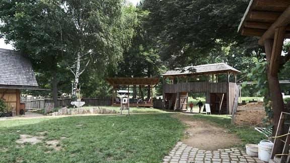 Ein kleiner Rasenplatz, der von Lehm-Holz-Hütten, einem Holztor und einer Bühne begrenzt ist.