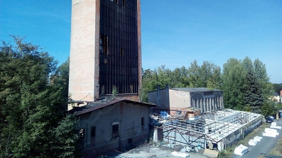 Ein Turm aus Beton mit kaputter Glasfront ragt aus Ruinen von Flachbauten hervor.