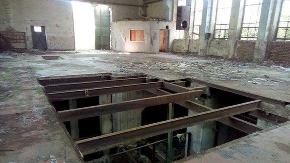 In einer maroden Werkhalle klafft ein großes Loch mit Stahlträgern im Boden.