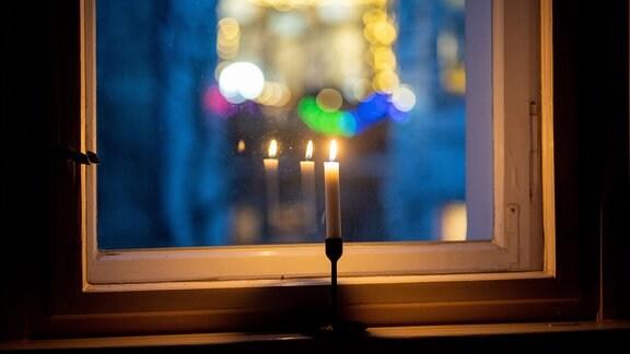 """Eine Kerze brennt in einem Fenster als Zeichen des gemeinsamen Gedenkens im Rahmen der Aktion """"#lichtfenster"""" für die Toten im Zusammenhang mit der Corona-Pandemie."""