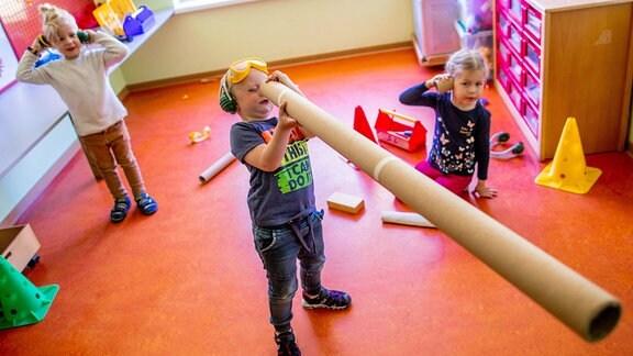 """Im Bauraum der Kindertagesstätte """"Anne Frank"""" hält der vierjährige Jan eine Papprolle."""