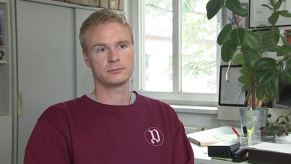 Ein junger blonder Mann mit roten Pullover sitzt vor einem Schreibtisch