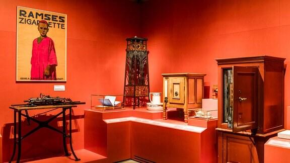 """Antiqitäten in einem Raum, darunter Tische, Schränke und ein Plakat auf dem """"Ramses Zigarette"""" steht"""