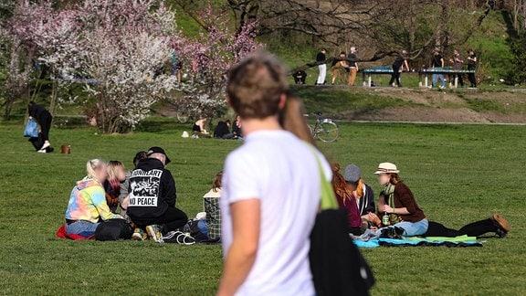 Zahlreiche Menschen haben sich in einem Park versammelt, gehen spazieren und spielen Tischtennis