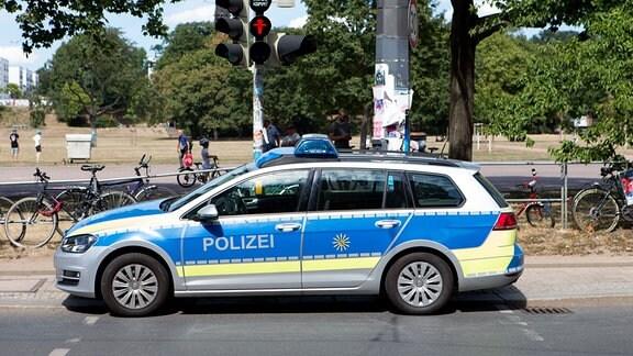 Während einer Demonstration im Dresdner Alaunpark steht ein Polizeifahrzeug auf einem Fuߟgängerüberweg und vor einer Ampel.