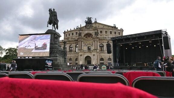 Blick auf die Semperoper. Davor stehten eine riesige leere Bühne und hunderte leere Stühle. Damit protestieren Künstler, Mitarbeiter der Veranstaltungsbranche, Techniker und Caterer für staatliche Hilfen in der Krise. Sie fühlen sich vergessen und nicht unterstützt.