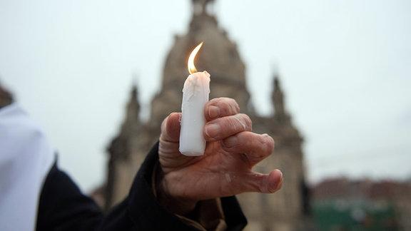 Kerze in der Hand einer Frau, während des Gedenkens an die Zerstörung der Stadt Dresden im Zweiten Weltkrieg