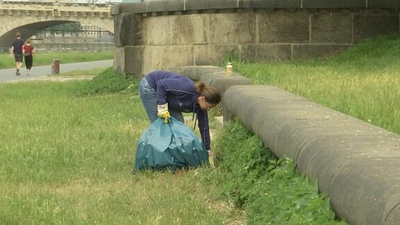 Eine Frau mit einem Müllbeutel in der Hand säubert eine Wiese.