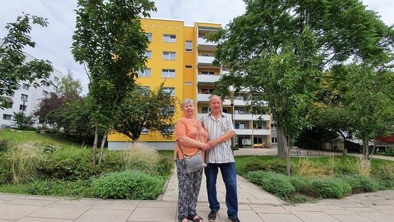 Ein Ehepaar steht vor einem Wohnblock mit altersgerechten Wohnungen.