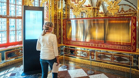 Eine Besucherin schaut in die ausgeraubte und nun ausgestellte Vitrine im Juwelenzimmer des Historischen Grünen Gewölbes im Residenzschloss in Dresden