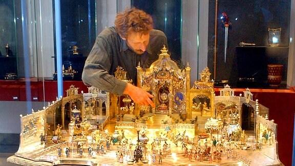 Der Restaurator Rainer Richter hebt im Neuen Grünen Gewölbe der Staatlichen Kunstsammlungen Dresden die Figur des Großmoguls Aureng-Zeb in seinen Miniaturhofstaat.
