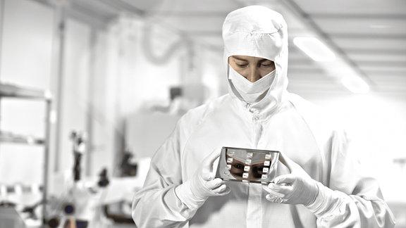 Ein Mitarbeiter steht in Schutzkleidung in einer Produktionsstätte.