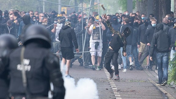 Ein Fan von Dynamo Dresden wirft einen Gegenstand in Richtung der Polizei.