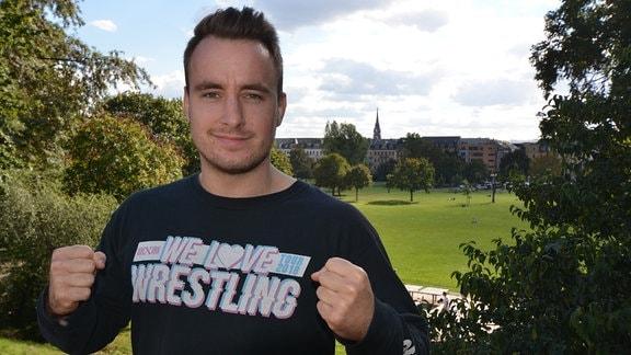 Ein junger Mann steht in einem Wrestling-Shirt vor einem Park.