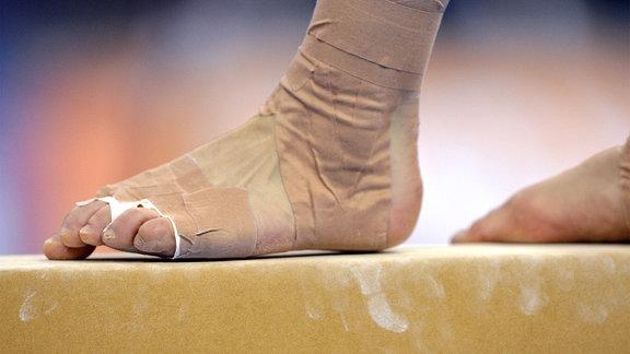 Detailaufnahme bandagierter Fuß auf Schwebebalken