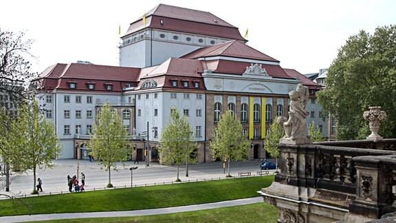 Das Schauspielhaus Dresden vom Zwinger aus fotografiert. Aufnahme im Frühjahr 2014. Auf dem Dach des Schauspielhauses hängen gelbe Fahnen. Zwei lange gelbe Fahnen mit Beschriftung schmücken auch die Vorderseite des Theatergebäudes.