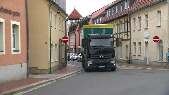 Ein Lkw fährt durch einen dicht bebauten Ort.