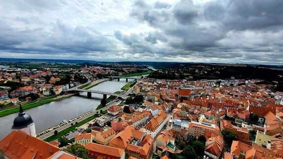 Blick über Dächer einer Altstadt, daneben ein Fluß und weite, grüne Hänge. Es ist der blick aus 62 Metern Höhe über die stadtr Meißen Richtung Dresden und Sächsische Schweiz.