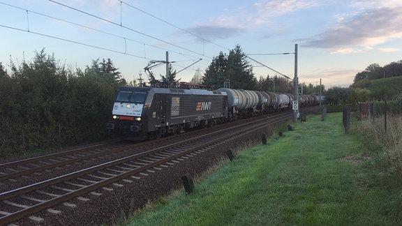 Eine schwarze E-Lok zieht einen Kesselwagenzug über eine zweigleisige Bahnstrecke.