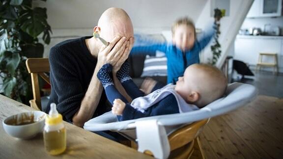 Ein Vater hält sich verzweifelt die Hande vor das Gesicht wäehrend er sein Baby füttert und ein weiteres Kind wütend im Hintergrund herumspringt.