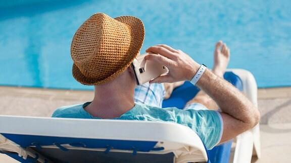 Mann liegt im Liegestuhl am Pool und telefoniert.