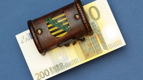 Bündel 200 Euro Geldscheine liegen in einer Schatztruhe mit Landeswappen des Flächenlands Sachsen