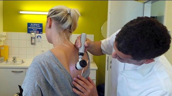 Eine junge Frau beit Hautcheck beim Dermatologen.