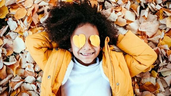 Lächelndes Mädchen mit Blättern in Herzform auf auf Augen liegt auf Laub im Park.