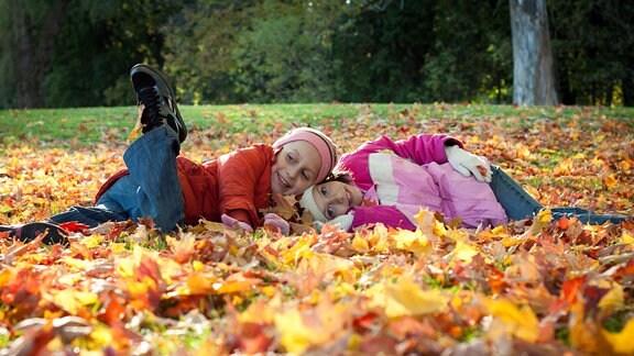 Kinder spielen im Laub.