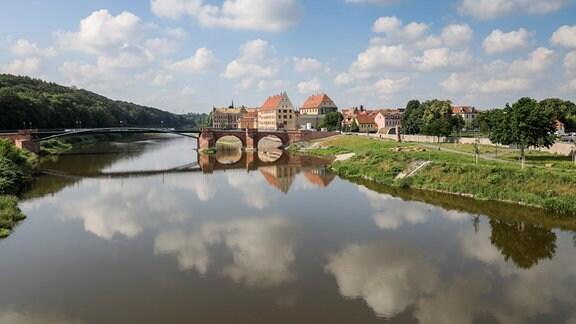 Die Pöppelmannbrücke über der Mulde, die Altstadt von Grimma und die darüber ziehenden Wolken spiegeln sich in dem Fluss.