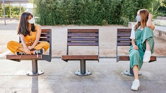 Junge Frauen mit Maske sitzen auf einer Bank