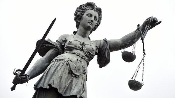 Eine Bronzestatue der römischen Göttin Justitia mit Waage und Richtschwert in der Hand