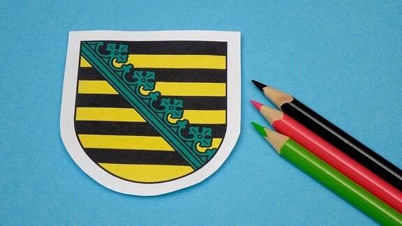 Ein grüner, ein roter und ein schwarzer Buntstift neben dem Wappen Sachsen