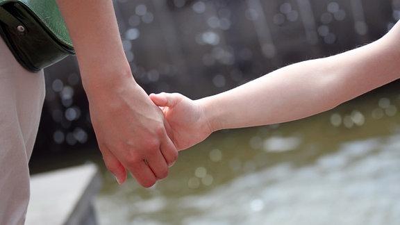 Erwachsenenhand hält Kinderhand