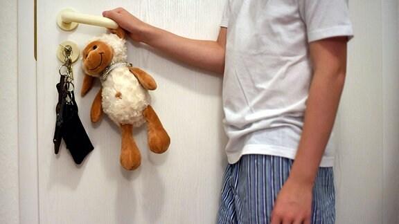 Ein Junge im Schlafanzug drückt mit einem Kuscheltier in der Hand die Klinke einer Wohnungstür