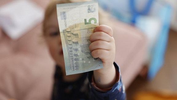 Kind hält Fünfeureoschein in der Hand.