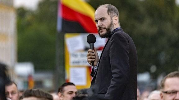 Martin Kohlmann von Pro Chemnitz spricht bei einer Demonstration vor dem Stadion vom Chemnitzer FC