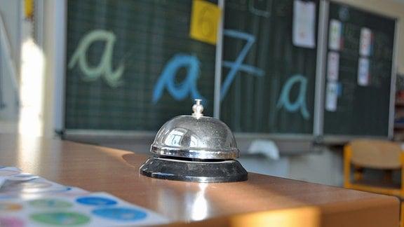 Eine Schulklingel steht auf dem Lehrertisch.