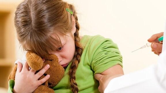 Ein Mädchen mit einem Teddybär soll eine Spritze bekommen