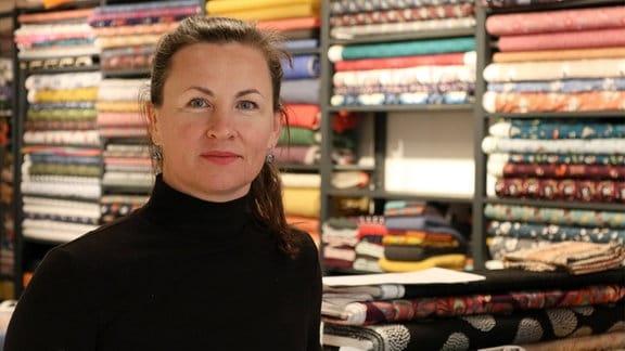 Frau in einem Einzelhandelsgeschäft schaut lächelnd in die Kamera.