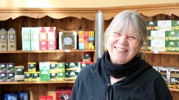 Frau in einem Einzelhandelsgeschäft schaut lachend in die Kamera.