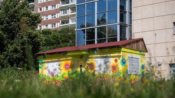 Ein bunter Container steht auf einer freien Fläche im Plattenbaugebiet Grünau in Leipzig