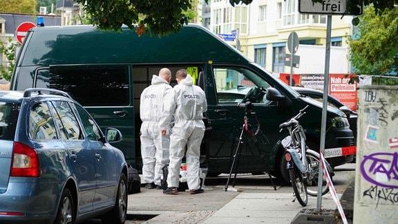 Kriminaltechniker an einem geparkten Auto.