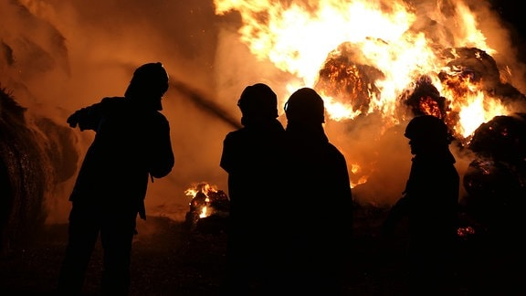 Feuerwehrleute stehen in Dunkelheit vor brennendem Stroh.