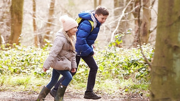Zwei Kinder laufen durch den Wald.