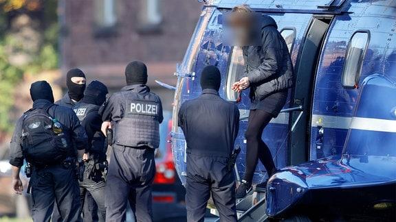 Lina E. steigt mit Handschellen in Karlsruhe aus einem Hubschrauber.