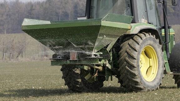 Mittels eines Traktors wird Kunstdünger auf einem Feld verteilt.