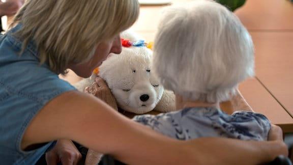 Eine Ergotherapeutin spricht 2013 in einem Seniorenpflegeheim für Menschen mit Demenz mit einer alten Frau.