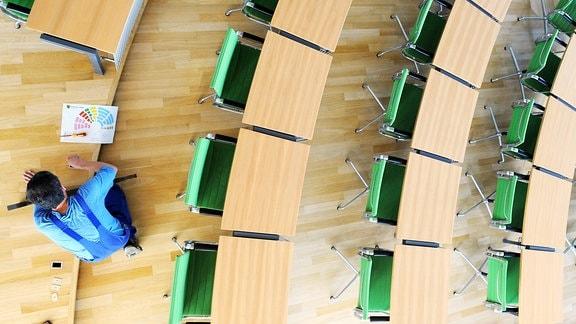 Ein Handwerker des sächsischen Landtages in Dresden hantiert am Mittwoch (09.09.2009) mit einem Sitzplan an den Stuhlreihen im Plenarsaal.