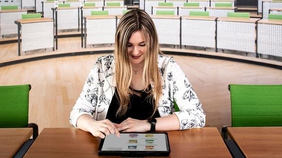 Eine junge Frau sitzt im Sächischen Landtag und testet auf einem Tablet-PC ihr Wissen über das Parlament.